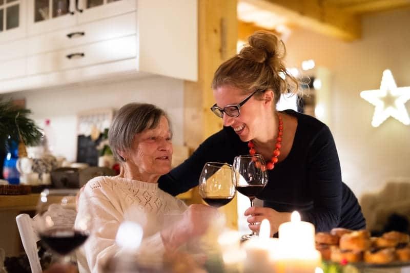 Mamãe apreciadora de bebidas tomando vinho com a filha na sala