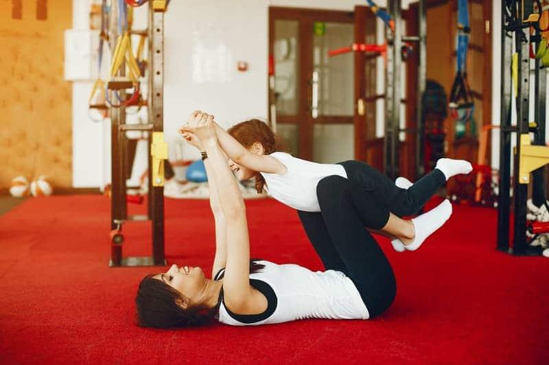 Mamãe fitness fazendo exercícios com a ajuda da filha