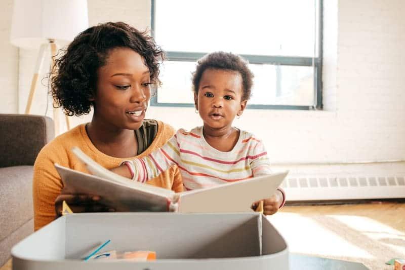 Mamãe que ama ler apreciando uma leitura com a filha no colo