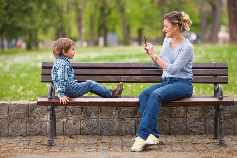 Mamãe tecnológica tirando foto do filho no parque